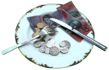 Money on a plate with knife and fork